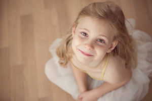 Portrait of smiling pretty diligent ballet girl sitting in white tutu at dance studio. Ower view