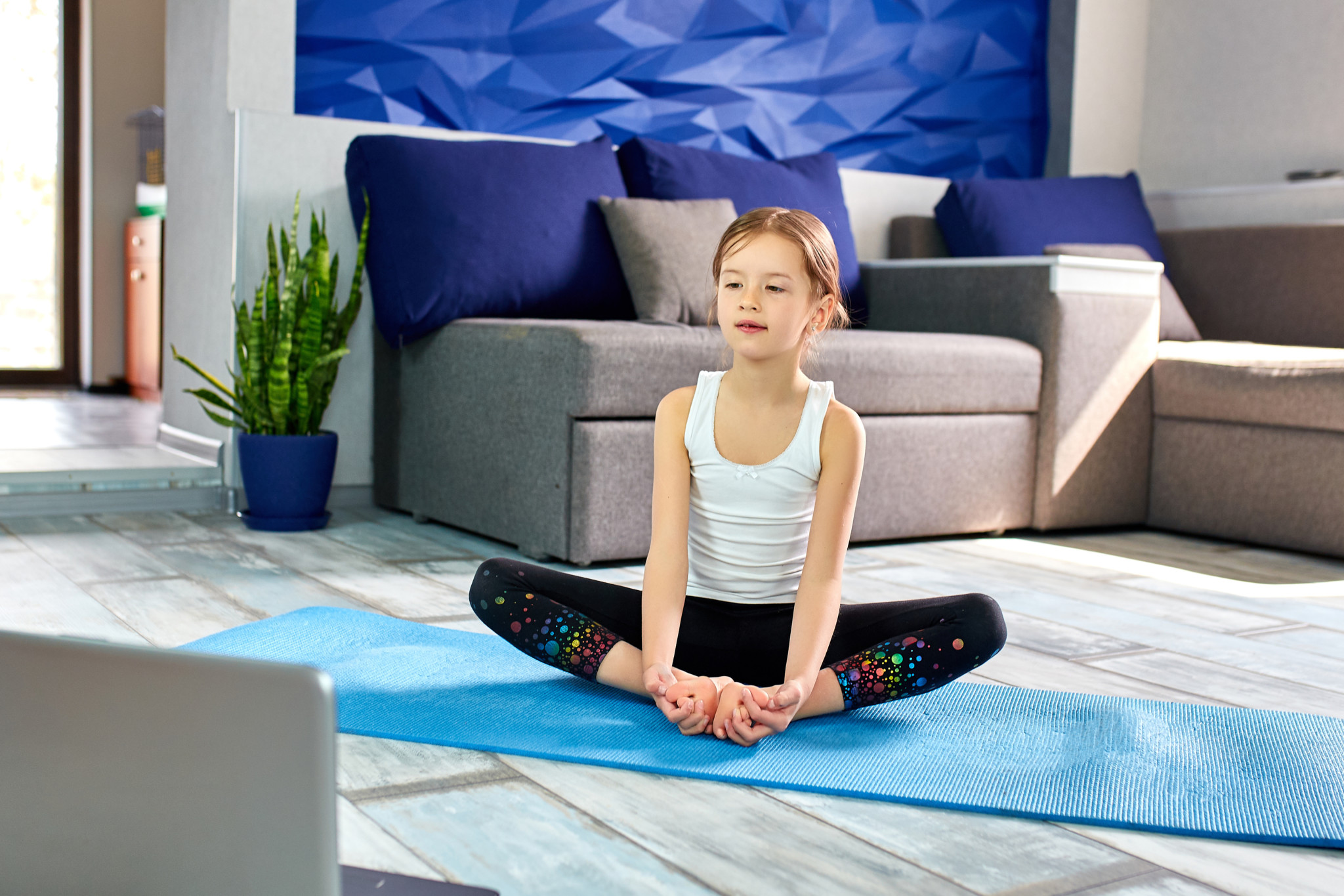 Little girl practicing yoga, stretching, fitness by video on notebook. Distant online education training, aerobic at home. Healthy lifestyle, coronavirus, stay home. Kids sport home quarantine.